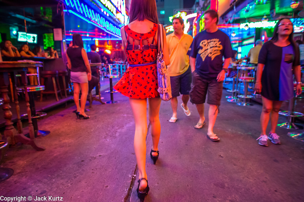 """21 JANUARY 2013 - BANGKOK, THAILAND:  A woman who works in a """"go-go bar"""" walks down Soi Cowboy, a red light district in Bangkok. Prostitution in Thailand is technically illegal, although in practice it is tolerated and partly regulated. Prostitution is practiced openly throughout the country. The number of prostitutes is difficult to determine, estimates vary widely. Since the Vietnam War, Thailand has gained international notoriety among travelers from many countries as a sex tourism destination. One estimate published in 2003 placed the trade at US$ 4.3 billion per year or about three percent of the Thai economy. It has been suggested that at least 10% of tourist dollars may be spent on the sex trade. According to a 2001 report by the World Health Organisation: """"There are between 150,000 and 200,000 sex workers (in Thailand).""""  PHOTO BY JACK KURTZ"""