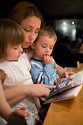 Loba reading to their two young children at bedtime. Grand Duchy of Luxembourg. Model Released. The image is part of a collection of images and documentation for Hungry Planet 2, a continuation of work done after publication of the book project Hungry Planet: What the World Eats.