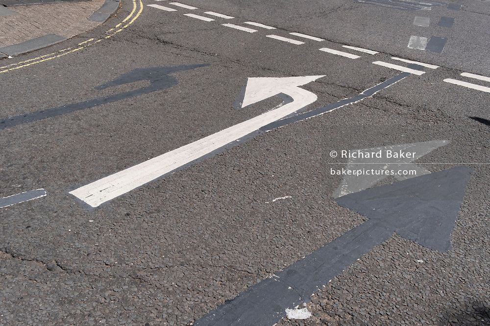An urban landscape of road markings and the ghosts of previous versions of turn left arrows, are seen from an elevated angle, in the road at Aldwych, on 23rd June 2021, in Westminster, London, England.