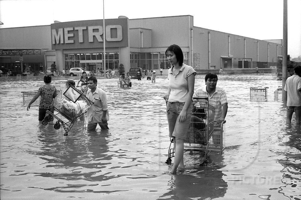 Hanoi, Vietnam.2008.The Metro Store is flooded but many people keep on shopping and use stratagems to avoid to wet their goods. The four November 2008, Hanoi, in Vietnam has been hit by its worst floods in 35 years.  Between Friday and Monday, more than 60 centimeters of rain paralyzed the city, causing massive damage and some twenty deaths. Metro Pham Van Dong