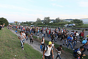 Hundreds of migrants walk along the the motorway from Budapest north towards Austria. Aftre becomming frustrated at the situation at nearby train stations the migrants decided to start the 350km journey themselves by foot.