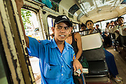 19 JUNE 2013 - YANGON, MYANMAR: A conductor on a Yangon bus. Yangon buses are generally overcrowded and in poor repair but as the economy improves newer, but still used, Japanese and Korean buses are being imported. Hundreds of bus routes criss-cross Yangon, providing the cheapest way of getting around the city. Most fares are less than the equivalent of .20¢ US.   PHOTO BY JACK KURTZ