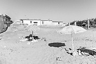 People sunbath nearby abusive houses on the beach of Castel Volturno, southern Italy, on August 12, 2013.