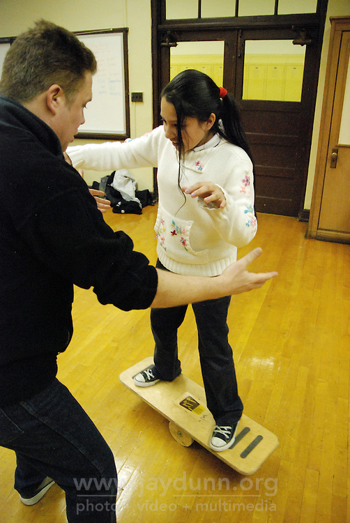 """USA, Chicago, IL, December 12, 2009. Nayeli Ferrer takes on the balance board.  Students in the """"At-Risk After School Program"""" at Maria Saucedo Scholastic Academy receive training in basic physics principles through an innovative new program called """"Circus Galactica"""" put on by Pros Arts, a non-profit organization founded in 1978 by professional artists dedicated to the Pilsen/Little Village communities. In a residency that directly integrates science and art, veteran circus performers Douglas Grew and Paul Lopez bring the importance of """"balance, focus and presentation"""" into hands-on lessons about gravity, inertia, and the dynamics of objects in motion. Photo for Hoy by Jay Dunn."""