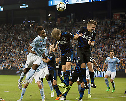 August 9, 2017 - Kansas City, Kansas, U.S - At foreground action (l-r), Sporting KC forward Latif Blessing #9 and San Jose Earthquakes midfielders Florian Jungwirth #23 and Tommy Thompson #22 vie for a header. (Credit Image: © Serena S.Y. Hsu via ZUMA Wire)