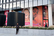 Three Londoners look at messages beneath a large billboard featuring an ecstatic young woman, on the exterior of a soon-to-open fitness club opposite Liverpool Station in the City of London, the capitals financial district, on 26th February 2021, in London, England.