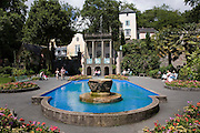 """Portmeirion, in North Wales, is a resort, where no one has ever lived. A self-taught Welsh architect named Sir Clough Williams-Ellis built it out of architectural salvage between the 1920s and 1970s, loosely based on his memories of trips to Portofino. Including a pagoda-shaped Chinoiserie gazebo, some Gothic obelisks, eucalyptus groves, a crenellated castle, a Mediterranean bell tower, a Jacobean town hall, and an Art Deco cylindrical watchtower. He kept improving Portmeirion until his death in 1978, age 94. It faces an estuary where at low tide one can walk across the sands and look out to sea. At high tide, the sea is lapping onto the shores. Every building in the village is either a shop, restaurant, hotel or self-catering accomodation. The village is booked out at high season, with numerous wedding receptions at the weekends. Very popular amongst the English and Welsh holidaymakers. Many who return to the same abode season after season. Hundreds of tourists visit every day, walking around the ornamental gardens, cobblestone paths, and shopping, eating ice-creams, or walking along the woodland and coastal paths, amongst a colourful assortment of hydrangea, rhododendrons, tree ferns and redwoods. The resort boasts two high class hotels, a la carte menus, a swimming pool, a lifesize concrete boat, topiary, pools and wishing wells. The creator describes the resort as """"a home for fallen buildings,"""" and its ragged skyline and playful narrow passageways which were meant to provide """"more fun for more people."""" It does just that.///Ornamental central gardens of Portmeirion village. Flanked by Dome Gallery, Gothic tower, Renaissance collonades, with lwans, flowerbeds, topiary, pools and fountains."""