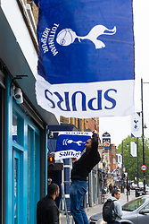 A man affixes Tottenham flags to a shopfront on Tottenham High Road ahead of  the club's Champions League final with Liverpool to be played at Atletico Madrid's Wanda Metropolitano Stadium in Madrid. Tottenham, London, May 29 2019.