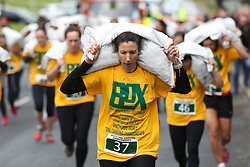 © Licensed to London News Pictures. 28/03/2016. Gawthorpe, UK. Penny Ditchfield leads the way during the ladies race of the 2016 World Coal Carrying Championships. The championships are held annually on Easter Monday in the small West Yorkshire town of Gawthorpe. The competition is a race which involves carrying a 20kg bag of coal up a steep incline to the finish line. Photo credit : Ian Hinchliffe/LNP