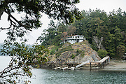 """Surrounded by the salty waters of Deception Pass, this remote house on Ben Ure Island can only be reached via boat. Aside from several private properties such as this, most of Ben Ure Island is within Deception Pass State Park, in Washington, USA. Elsewhere on the island, you can rent a quiet State Park cabin. Photographed from the park's scenic Goose Rock Perimeter Trail on Whidbey Island. In the late 1880s, Ben Ure and his partner Lawrence """"Pirate"""" Kelly ran a profitable but illegal business smuggling Chinese immigrants for local labor. Local stories say he would hide the immigrants wrapped in burlap bags which could be tossed overboard if US Customs agents were encountered. Tidal currents would carry the immigrants' bodies northwest to San Juan Island to what became known as Dead Man's Bay -- now called Deadman Bay, bordering Lime Kiln Point State Park. Deception Pass is a strait of water separating Whidbey Island from Fidalgo Island, and connects Skagit Bay (part of Puget Sound) with the Strait of Juan de Fuca, which are all part of the Salish Sea. Deception Pass is the most-visited State Park in Washington."""