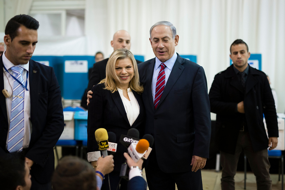 Israeli Prime Minister Benjamin Netanyahu and his wife, Sara, are surrounded by members Netanyahu's security detail, as they speak to the press after casting their vote for the Likud party primary elections, at a polling station in Jerusalem, on December 31, 2014. Netanyahu is widely expected to retain the helm of the right-wing Likud party ahead of Israel's general elections in March.