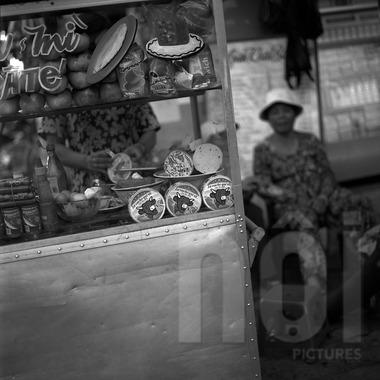 Black&white film photograph of a sandwich stand selling French cheese 'la vache qui rit' and cold cut sandwiches, Ho Chi Minh City, Vietnam, Southeast Asia