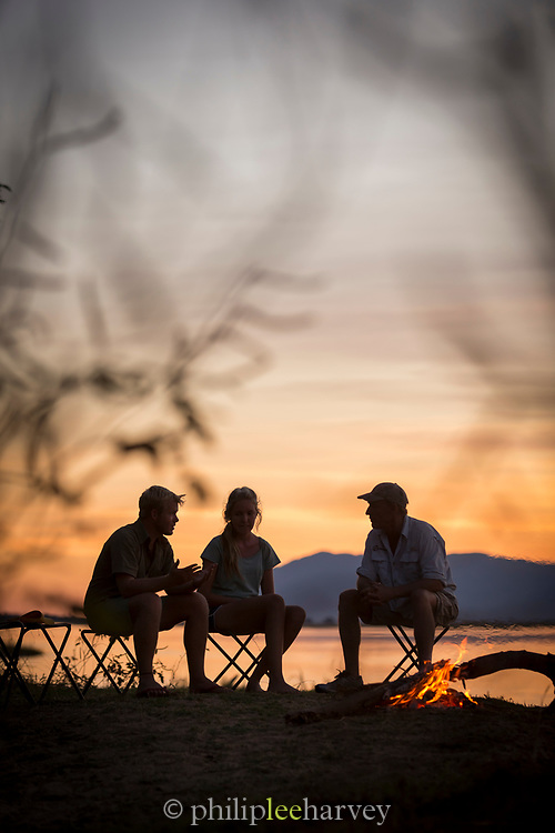 Tourists talking to guide at sunset by lower Zambezi River in Mana Pools National Park, Zambia