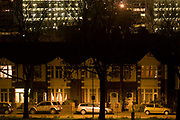 Looking across south London towards Edwardian homes and block of flats in the darkness of the suburbs. It is late one evening in central London, in a suburb known as Herne Hill, SE24 in the borough of Lambeth. We see across the metropolis from quiet and expensive period homes, whose owners would typically be white middle-class, across to the blocks of flats (apartments) in the Loughborough Estate, a far rougher location for street gangs and high crime rates. Owners' cars are parked under streetlights and ash trees and lights shine out from living rooms and bedrooms.