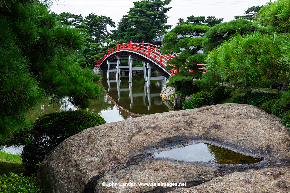 Arched Bridge at Banshoen Garden - Nakatsu Banshoen - Marugame is famous for its historic castle, but few realize that there is an amazing garden hidden nearby. Nakatsu Banshoen was built in 1688 for the second generation feudal lord of Marugame. It contains a winding path around a lovely pond garden full of islands.  This is a daimyo garden and one of the largest and most famous gardens in Kagawa prefecture. Eight islands of the eight most scenic places of Omi were created in the pond which was modelled on Lake Biwa. The garden is also covered with more than 1,500 pine trees plus hundreds of Satsuki, making use of the surrounding landscape in the design of a garden in Seto Inland Sea.