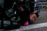 Riot police officer pushes protesters head down to the ground after their airport protest on September 1st, 2019 at highway between Hong Kong International Airport to Tung Chung MTR Station in Tung Chung in Hong Kong, China.