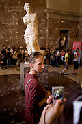A girl poses near Aphrodite, otherwise known as the Venus de Milo in the Louvre art museum. The ancient Greek statue is one of the most famous works of ancient Greek sculpture, created sometime between 130 and 100 BC. The Aphrodite (Greek goddess of love and beauty  and Venus to the Romans) is a marble sculpture, slightly larger than life size at 203 cm high. The arms and original plinth were lost following the discovery. From an inscription that was on its plinth, it is thought to be the work of Alexandros of Antioch; earlier, it was mistakenly attributed to the master sculptor Praxiteles.