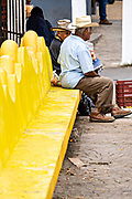 Elderly Mexican men sit on a bright yellow bench at a park in Santiago Tuxtla, Veracruz, Mexico.