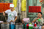 11 SEPTEMBER 2013 - BANGKOK, THAILAND:  A diner, right, watches a worker serve customers at a curry stand in the Chinatown section of Bangkok. Thailand in general, and Bangkok in particular, has a vibrant tradition of street food and eating on the run. In recent years, Bangkok's street food has become something of an international landmark and is being written about in glossy travel magazines and in the pages of the New York Times.        PHOTO BY JACK KURTZ