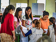 08 NOVEMBER 2015 - YANGON, MYANMAR:  People get their ballots in their polling place in a public school in North Okkalapa, a township outside central Yangon. The citizens of Myanmar went to the polls Sunday to vote in the most democratic elections since 1990. The National League for Democracy, (NLD) the party of Aung San Suu Kyi is widely expected to get the most votes in the election, but it is not certain if they will get enough votes to secure an outright victory. The polls opened at 6AM. In Yangon, some voters started lining up at 4AM and lines were reported to long in many polling stations in Myanmar's largest city.     PHOTO BY JACK KURTZ