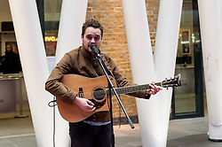 © Licensed to London News Pictures. 16/03/2016. London, UK. Guitarist, Charlie Hole, performs.  Buskers and street performers entertain morning commuters in King's Cross station, as this year's Busk in London programme is launched.  Supported by the Mayor of London, the festival joins the International Busking Day and National Busking Day initiatives to celebrate street performances. Photo credit : Stephen Chung/LNP