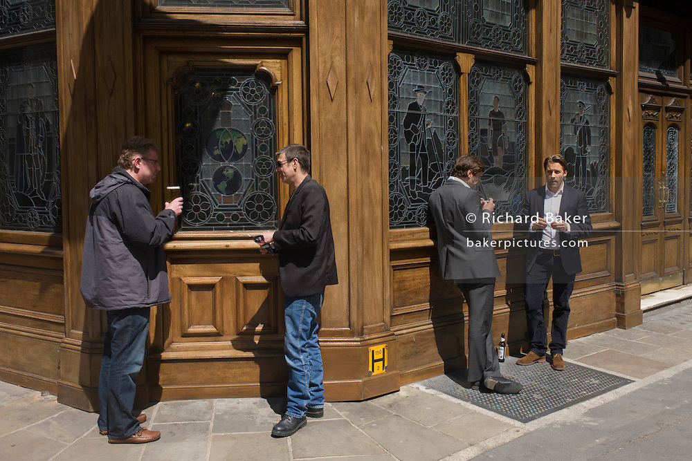 Lunchtime drinking blokes stand in the street, outside a central London pub.