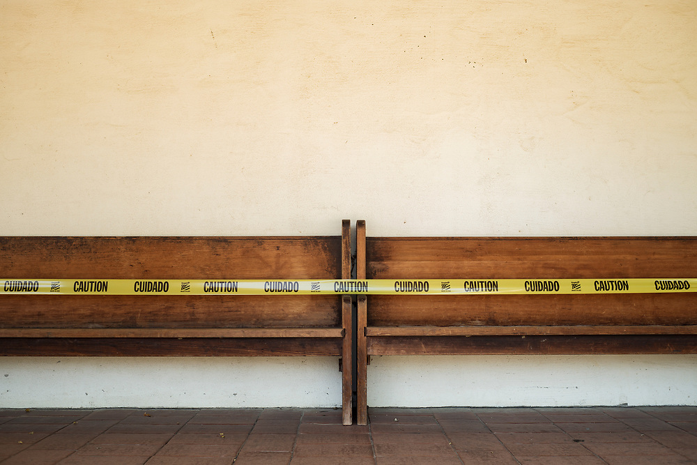 Caution tape prevents visitors from gathering on benches outside of Old Mission San Juan Bautista in San Juan Bautista, Calif. on July 26, 2020.