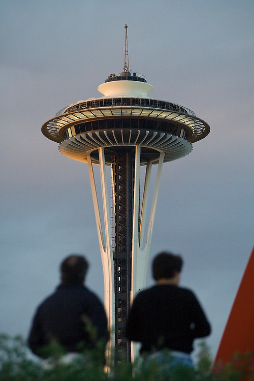 Two people sit outside at the Seattle Art Museum Olympic Sculpture Park in Seattle, Washington, with the Space Needle rising above them.