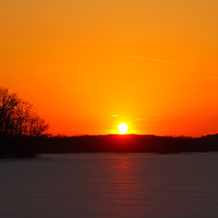 """""""Great Ball of Fire""""<br /> <br /> A radiant sunset over a snow covered, frozen Michigan lake!<br /> A wonderful orange glow fills the sky, illuminates the snow, and turns the bare trees into dark silhouettes!!<br /> <br /> Sunset Images by Rachel Cohen"""