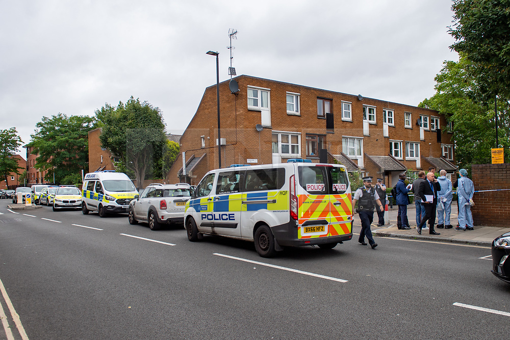 © Licensed to London News Pictures. 04/07/2020. London, UK. Forensic investigators look over the crime scene alongside a row of police vehicles on Roman Way in Islington. Metropolitan Police Service officers were called at 15:20BST on Saturday, 4 July to Roman Way N7 following reports of shots fired. Officers attended with London Ambulance Service (LAS) and found a man, believed to be aged in his early 20s, suffering from gunshot injuries. Despite their best efforts, he was pronounced dead at the scene. Photo credit: Peter Manning/LNP