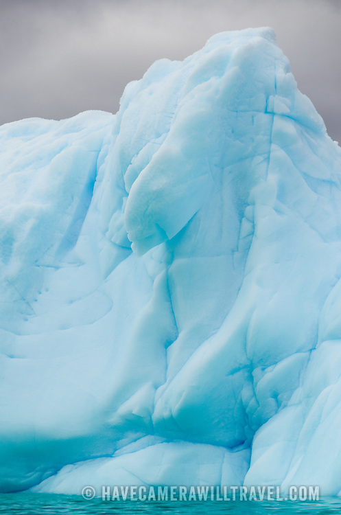Intricately shaped icebergs floating in an iceberg graveyard bunched in a cove near Melchior Island in Antarctica.