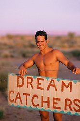 shirtless man standing in front of a dream catcher sign in the desert of New Mexico