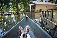 Sept. 2, 2016  My feet in Frank Bonifay's canoe as Bonifay paddles us to  one of his properties in Iberville Parish that is in the Spanish Lakes Region, following the 1000 year flood. The area was flooded by back flow, leading to a situation where there area now has standing water trapped in it. The local government made cuts in a road to give the water a way to escape from the area. It will take up to thrity days before the water is ecpected to go down completely.