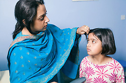 Mother brushing her young daughter's hair,