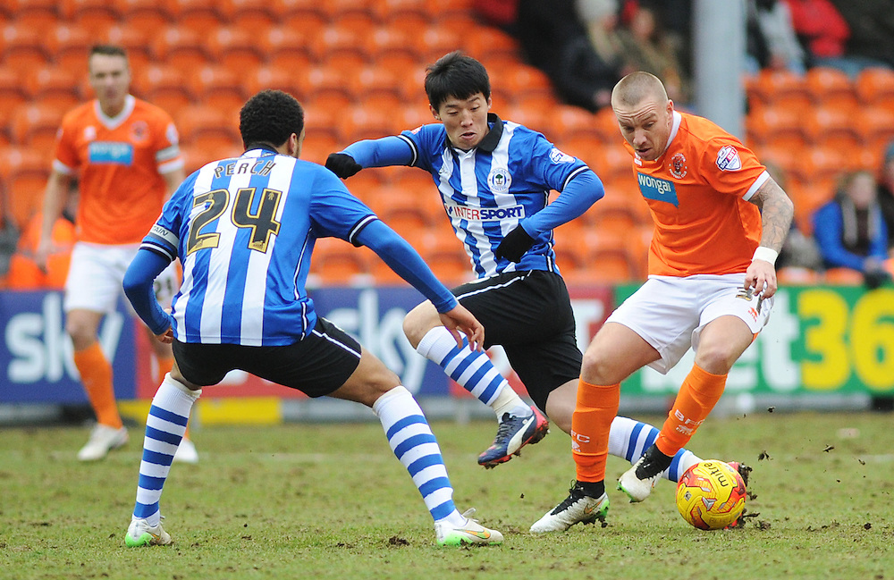Blackpool's Jamie O'Hara under pressure from Wigan Athletic's James Perch (left) and Kim Bo-Kyung<br /> <br /> Photographer Kevin Barnes/CameraSport<br /> <br /> Football - The Football League Sky Bet Championship - Blackpool v Wigan Athletic - Saturday 28th February 2015 - Bloomfield Road - Blackpool<br /> <br /> © CameraSport - 43 Linden Ave. Countesthorpe. Leicester. England. LE8 5PG - Tel: +44 (0) 116 277 4147 - admin@camerasport.com - www.camerasport.com