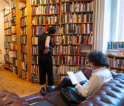 Man reading book  inside St Georges secondhand bookshop in Prenzlauer berg, Berlin, Germany