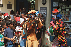 Clowns singing and playing guitars to entertain children on the streets of Havana; Cuba,