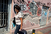 Street scene in Omonia. Woman walks past a building covered in graffiti. Visitors to Athens can't help but notice the amount of graffiti in the city. Any surface that can be sprayed upon is covered with a maddening number of signatures and designs. Beautifully restored neo-classic houses from the late 19th Century usually have a few days or weeks before they are covered in graffiti and owners find themselves in a war that they eventually lose and surrender to the kids. Graffiti in Athens is as old as the city itself. In ancient times graffiti was carved into buildings, in fact the word comes from the Greek graphi which means to write. The most disturbing aspect of the graffiti besides the volume of it, is the way some of the kids whose artistic ability begins and ends with their names (tags), have defaced some of the real works of art. Athens is the capital and largest city of Greece. It dominates the Attica periphery and is one of the world's oldest cities, as its recorded history spans around 3,400 years. Classical Athens was a powerful city-state. A centre for the arts, learning and philosophy.