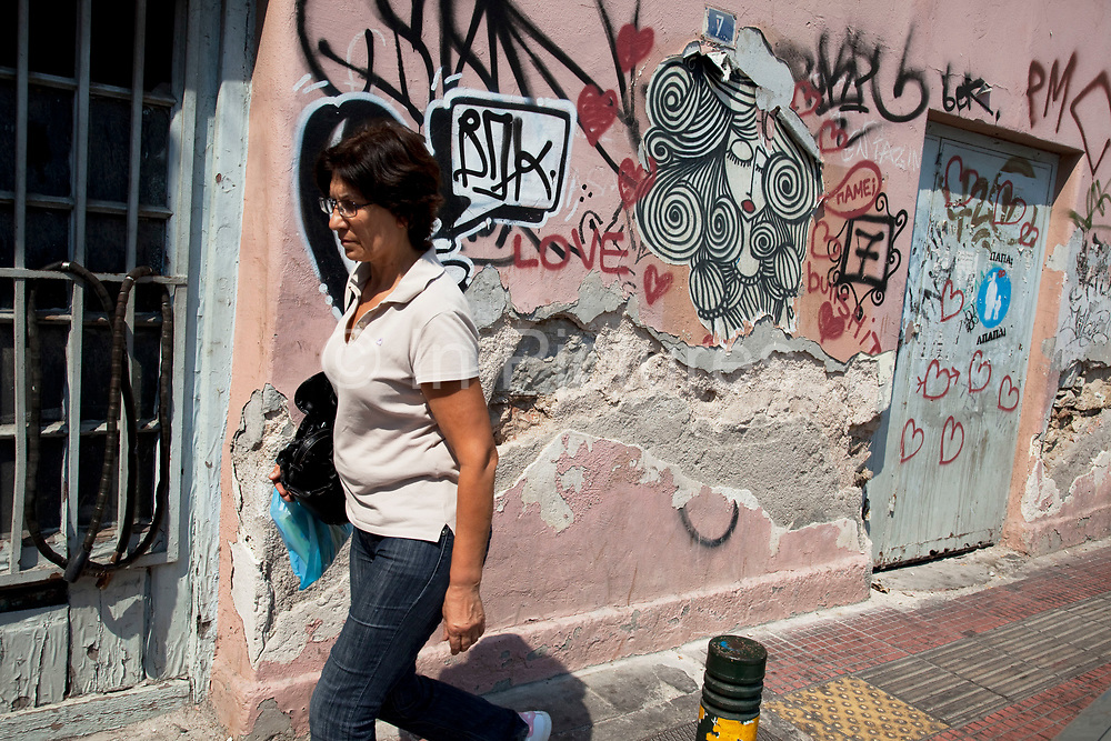 Street scene in Omonia. Woman walks past a building covered in graffiti. Visitors to Athens can't help but notice the amount of graffiti in the city. Any surface that can be sprayed upon is covered with a maddening number ofsignatures and designs. Beautifully restored neo-classic houses from the late 19th Century usually have a few days or weeks before they are covered in graffiti and owners find themselves in a war that they eventually lose and surrender to the kids. Graffiti in Athens is as old as the city itself. In ancient times graffiti was carved into buildings, in fact the word comes from the Greek graphi which means to write. The most disturbing aspect of the graffiti besides the volume of it, is the way some of the kids whose artistic ability begins and ends with their names (tags), have defaced some of the real works of art. Athens is the capital and largest city of Greece. It dominates the Attica periphery and is one of the world's oldest cities, as its recorded history spans around 3,400 years. Classical Athens was a powerful city-state. A centre for the arts, learning and philosophy.