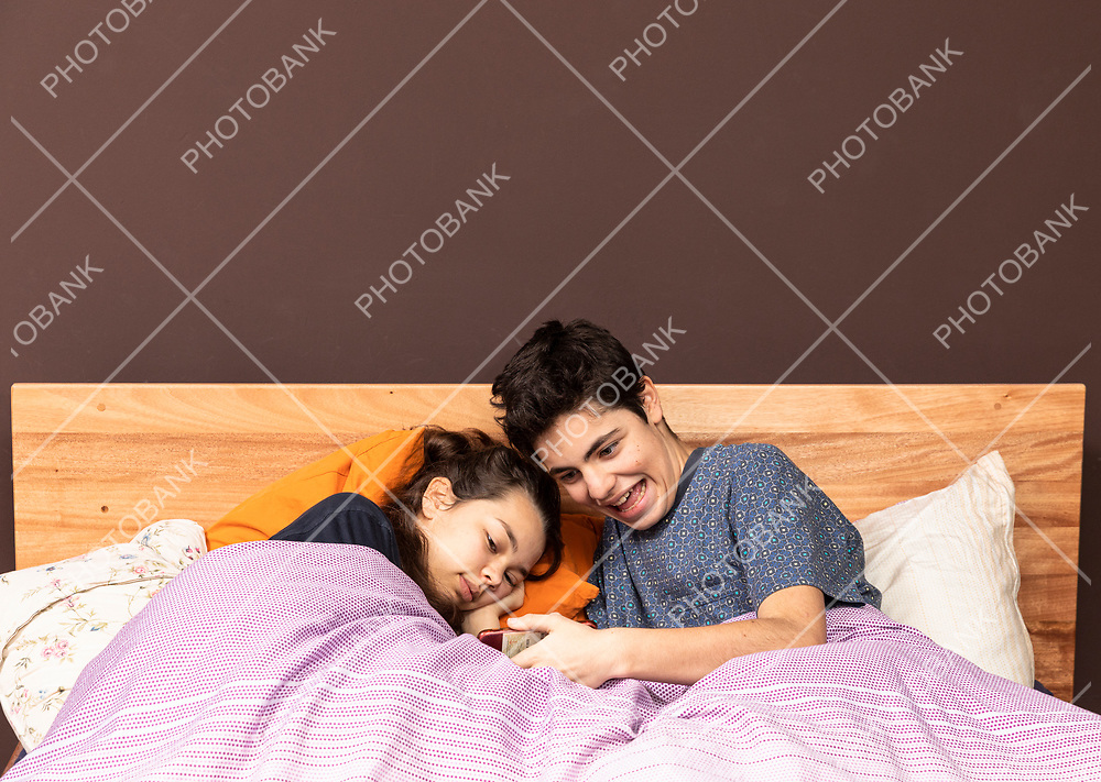 Couple in bed watching a movie or news together on a phone.
