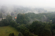 Mistflarden hangen over de bomen bij het dorp Ellecom (in de achtergrond te zien). Gefotografeerd vanuit een hete luchtballon<br /> <br /> Fog above the trees at Ellecom (in the back of the photo). Photographed from an air balloon