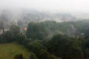 Mistflarden hangen over de bomen bij het dorp Ellecom (in de achtergrond te zien). Gefotografeerd vanuit een hete luchtballon<br /> <br /> Fog above the trees at Ellecom (in the back of the photo). Photographed from an air balloon