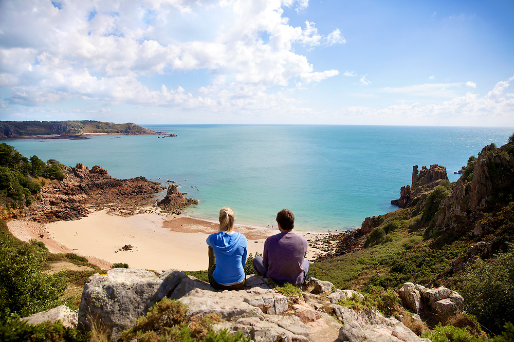 Couple sat on a cliff edge looking out over the south coast and Beauport Bay on a sunny summer day in Jersey, CI
