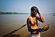 """Colombia, Amazonas, 2010.El baño de Yuché. <br /> Yuché, Dios de la comunidad Tikuna, ha envejecido y, mirándose en el agua, se da cuenta de que se acerca la muerte. Así comienza el mito aborigen. En la foto, Jesús Rodríguez enjuaga su rostro joven en el Río Amazonas, pero no logra borrar la marca del huito que los tikunas llevan a su cuerpo después de extraer la pintura del fruto selvático. Por esto los conocen como """"pieles negras"""". <br /> Yuché bath. <br /> Yuché,  Tikuna's God of community, has aged and looking in the water,  realizes that death is approaching. So begins the Aboriginal myth. In the photo, Jesus Rodriguez rinses his young face in the Amazon River, but he does not manage to erase the mark of 'huito' that tikunas takes to their body after extracting the painting of the sylvan fruit.  This is why they are known as """"black skins"""". <br /> <br /> ENSAYO: UN FRÁGIL TESORO , AMAZONAS. / AMAZON FRAGIL TREASURE<br /> <br /> Amanece. Aves y reptiles de todas las especies comienzan a cantar. El río está tibio y hace calor. El Amazonas, que nunca deja de correr, ahora cobra vida con la llegada del día. Mujeres y hombres se acercan a su orilla. Lavan, comparten, pescan, trabajan, aman y, en algunos casos, también trafican en ésta, el área con mayor biodiversidad del mundo, y el río más caudaloso y extenso. En sus puertos, la Latinoamérica amazónica mezcla sus culturas e intercambia productos, entre ellos, los que la convierten en zona de peligro: cocaína y armas también encuentran refugio en la espesura de la selva. Los tikuna son los habitantes de estas tierras ardientes, donde las altas temperaturas casi sobre el nivel del mar desafían a la raza más fuerte. Conquistados por los españoles estos indígenas resistieron hasta la masacre. Hoy solo quedan 27 mil tikunas repartidos en tres países: Colombia, Perú y Brasil. En las fotografías, se retrata la cotidianidad del tikuna colombiano que, a quinientos años de su colonización, conserva poco de su auténtica"""