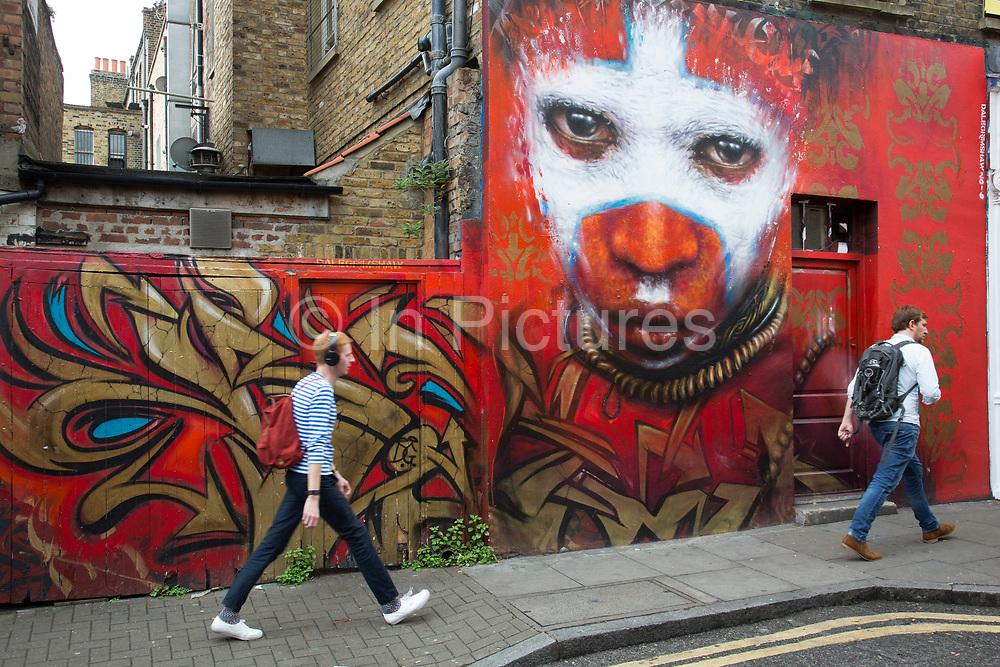 Tribal character Street art by Dale Grimshaw in the Brick Lane area of Shoreditch, East London, United Kingdom. Street art in the East End of London is an ever changing visual enigma, as the artworks constantly change, as councils clean some walls or new works go up in place of others. While some consider this vandalism or graffiti, these artworks are very popular among local people and visitors alike, as a sense of poignancy remains in the work, many of which have subtle messages.