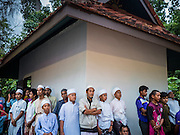 17 JUNE 2015 - YAHA, YALA, THAILAND: Thai Muslims take shelter from the rain during the Hilal in Yaha. During a break in the rain and clouds, people saw the crescent moon and the beginning of Ramadan was declared. Thousands of people came to Yaha District in Yala province of Thailand for the Hilal - the first sighting of the crescent moon that marks the official beginning of the Muslim holy month of Ramadan. Despite cloudy weather and intermittent rain showers, the moon was sighted and religious leaders declared the official beginning of Ramadan.    PHOTO BY JACK KURTZ