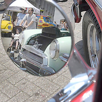 Reflecting in the side mirror of a Bel Air car Amy McGeady walks with her husband John and son Luke, 2, through the many cars on display on Pier 21 in Galveston, 05/29/04.  (Photo by Kim Christensen)