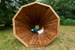 """© Licensed to London News Pictures. 08/07/2021. LONDON, UK. A staff member experiences """"RUUP: Forest Megaphones"""" by Birgit Olgus, one of three giant wooden megaphones.  Preview of Summer of Sound where six striking large-scale sound installations takeover Wakehurst, Kew's wild botanic garden in Sussex.  Artists have created installations offering moments to pause and feel connected to nature through a symphony of sounds created or inspired by the natural world.  Summer of Sound runs 9 July to 12 September 2021. Photo credit: Stephen Chung/LNP"""
