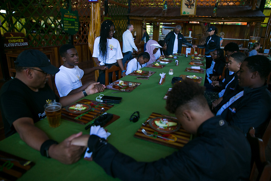 Everyone holds hands and prays before lunch is served.