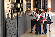 Children in school uniforms play with a payphone in the town of Valle de Angeles, Honduras on Friday April 26, 2013.
